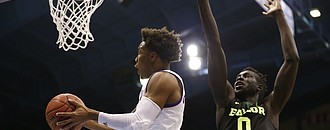 Kansas guard Devonte' Graham ducks under the Baylor forward Jo Lual-Acuil Jr. (0) for a bucket during the second half, Wednesday, Feb. 1, 2017 at Allen Fieldhouse.