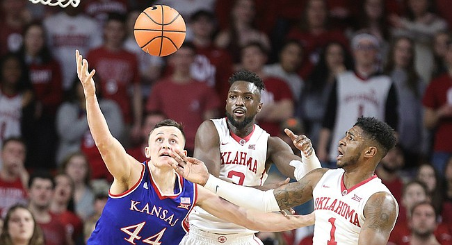 Kansas forward Mitch Lightfoot (44) fights for a ball with Oklahoma forward Khadeem Lattin (3) and Oklahoma guard Rashard Odomes (1) during the first half at Lloyd Noble Center on Tuesday, Jan. 23, 2018 in Norman, Oklahoma.