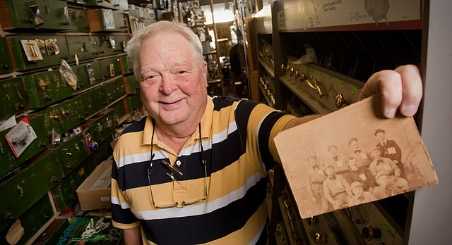 In this file photo from November 2010, Rod Ernst of Ernst & Son Hardware, 826 Massachusetts St., is pictured with a group photograph that includes his grandfather, Philip Ernst, far left in middle row, which he believes dates back to the early 1880's