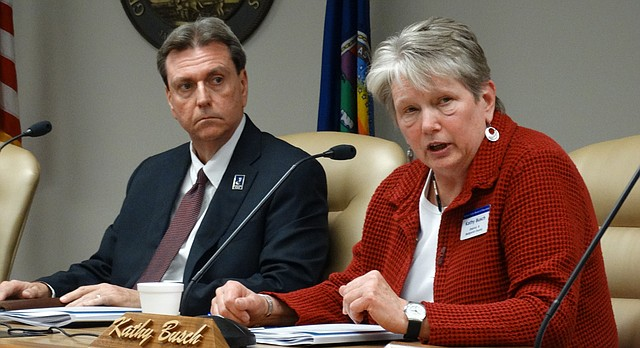 Kansas Education Commissioner Randy Watson, left, listens while State Board of Education member Kathy Busch voices her support for embattled Deputy Commissioner Dale Dennis.