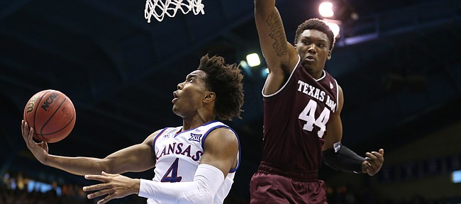 Kansas guard Devonte' Graham (4) swoops under the bucket for a shot against Texas A&M forward Robert Williams (44) during the second half, Saturday, Jan. 27, 2018 at Allen Fieldhouse.