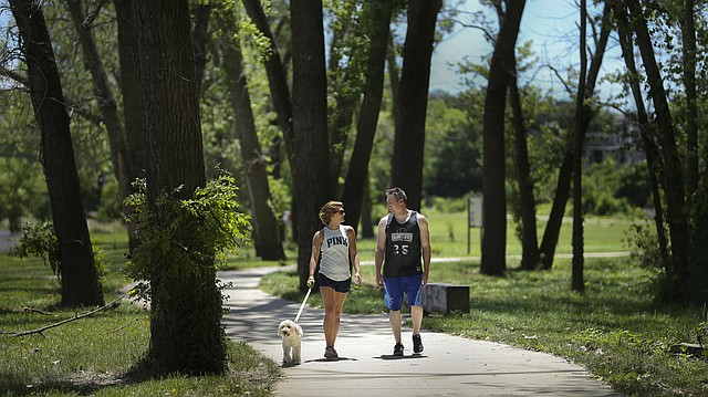 In this file photo from June 23, 2017, Staci Burch, of Lawrence, and Mark Patterson, of Overland Park, enjoy a walk along the Burcham Park Trail with Burch's dog Zara.