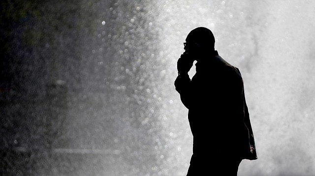 In this Thursday, Oct. 11, 2012 file photo, a pedestrian talking on a cellphone is silhouetted in front of a fountain at John F. Kennedy Plaza, also known as Love Park in Philadelphia. Two government studies that bombarded rats and mice with cellphone radiation found a weak link to some heart tumors, but the research, released Feb. 2, 2018, does not provide any clear answers about the safety of the devices. (AP Photo/Matt Rourke)