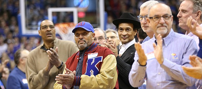 Players from the Ted Owens years applaud as their coach is honored during a halftime ceremony in recognition of 120 years of Kansas basketball.