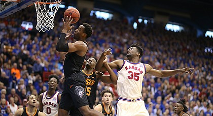 Kansas center Udoka Azubuike (35) watches as Oklahoma State forward Cameron McGriff (12) pulls down a rebound during the first half, Saturday, Feb. 3, 2018 at Allen Fieldhouse.