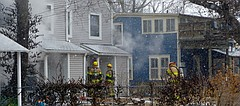 Smoke escapes from a duplex Sunday morning at 1042 New Jersey St. as Lawrence firefighters try to contain the fire.