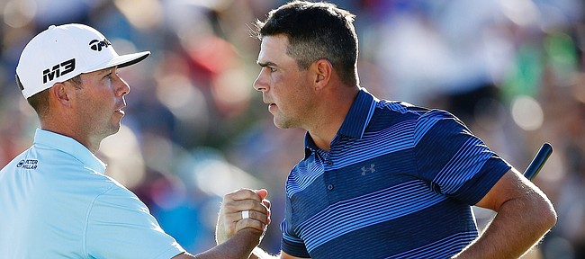 After winning a one-hole playoff, Gary Woodland, right, shakes hands with Chez Reavie, left, on the 18th green during the final round of the Waste Management Phoenix Open golf tournament Sunday, Feb. 4, 2018, in Scottsdale, Ariz. (AP Photo/Ross D. Franklin)