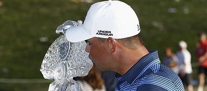 Gary Woodland kisses the championship trophy for photographers after his one-hole playoff win in the final round of the Waste Management Phoenix Open golf tournament Sunday, Feb. 4, 2018, in Scottsdale, Ariz. (AP Photo/Ross D. Franklin)