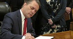Kansas Gov. Jeff Colyer signs an executive order on sexual harassment as members of his Cabinet watch, Monday, Feb. 5, 2018, at the Statehouse in Topeka, Kan. (AP Photo/John Hanna)