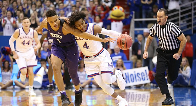 Kansas guard Devonte' Graham (4) picks off a pass to TCU guard Desmond Bane (1) during the first half on Tuesday, Feb. 6, 2018 at Allen Fieldhouse.