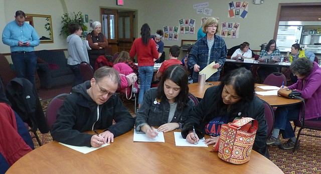David Carttar, left, his daughter Gabriela Carttar and Claudia Oleo write letters Saturday at the Plymouth Congregational Church to the U.S. Immigration and Customs Enforcement asking it stay the deportations of Lawrence residents Raju Ahmed and Syed Jamal. Susan Baker-Anderson, director of children's education at Plymouth, said she and Dani Lotton-Barker, organized the event in support of their friend Jamal. About 250 wrote letters at the church, she said. A similar hourlong letter-writing campaign followed at the Lawrence Islamic Center with the conclusion of the Plymouth event.