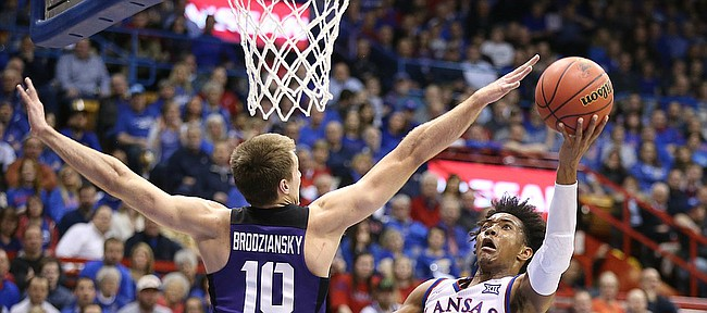 Kansas guard Devonte' Graham (4) maneuvers for a shot against TCU forward Vladimir Brodziansky (10) during the first half on Tuesday, Feb. 6, 2018 at Allen Fieldhouse.