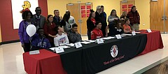 LHS athletes pose for pictures with their families at Lawrence High signing day. Athletes, from left to right: Ekow Boye-Doe, Austin Quick, Dante Jackson, Jalen Dudley, Kristian Russell, Harrison King.