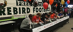 Free State football players sign their letters of intent during a ceremony Wednesday in the school's Black Box Theatre. From left, Jalan Robinson (undecided), Gabe Clark (Central Missouri), Tanner Cobb (Baker), Nathan Spain (Baker), Gage Foster (Baker), David Johnson (Emporia State) and Spencer Roe (Kansas).