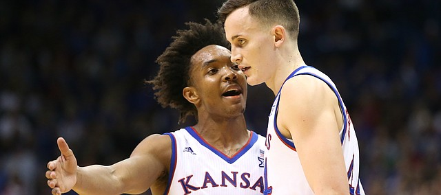 Kansas guard Devonte' Graham (4) talks with Kansas forward Mitch Lightfoot (44) during a break in action in the second half on Tuesday, Feb. 6, 2018 at Allen Fieldhouse.