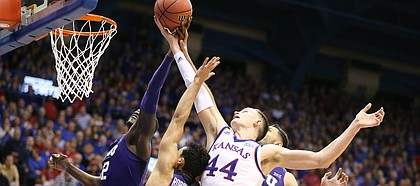 Kansas forward Mitch Lightfoot (44) fights for a ball with several TCU players during the first half on Tuesday, Feb. 6, 2018 at Allen Fieldhouse.