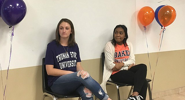 Free State soccer players, Sydni Beeley (Truman State), left, and Maya Hodison (Baker University) celebrate their signings Wednesday in the school's Annex.