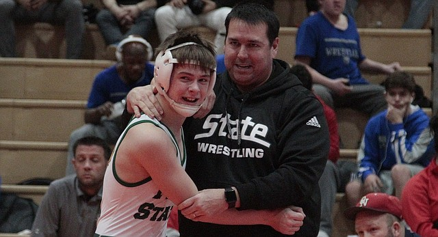 Free State freshman Caleb Streeter hugs coach Mike Gillman after winning the 113-pound championship match at the Sunflower League tournament on Saturday at Olathe East. Streeter and senior Elijah Denmark won their weight classes to lead the Firebirds to second place. Gillman was named the Sunflower League Coach of the Year.