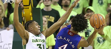 Kansas guard Devonte' Graham (4) is defended by Baylor Bears forward Terry Maston (31) on the shot during the second half, Saturday, Feb. 11, 2018 at Ferrell Center in Waco, Texas.