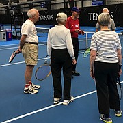 Coach Dick Wedel, smiling at center, gets a group of senior participants prepped for tennis class on Feb. 2, 2018 at the Jayhawk Tennis Center, 233 Rock Chalk Lane. Wedel was a coach at Lawrence High School for more than 30 years. He is now one of several certified coaches who teach at the Jayhawk Tennis Center.