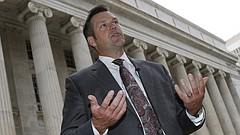 In this file photo from Aug. 23, 2016, Kansas Secretary of State Kris Kobach responds to questions outside the 10th U.S. Circuit Court of Appeals after delivering an argument in a legal fight over how the state of Kansas enforces its proof-of-citizenship requirement for voters who register at motor vehicle offices.