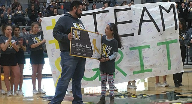 Free State teacher Nolan Henderson holds onto a check from the school's spirit squad during halftime of the Free State boys basketball game on Tuesday, Feb. 13, 2018 at FSHS alongside his daughter Ella Avant. His 4-month-old son, Grit, is battling a rare skeletal muscle cancer and the school held a T-shirt fundraiser.