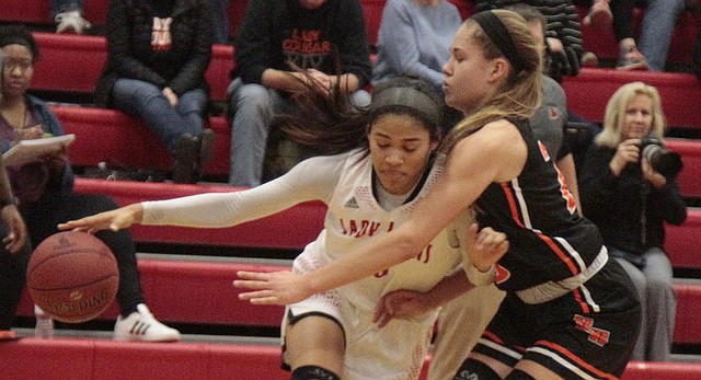 Lawrence High senior E'lease Stafford tries to dribble past Shawnee Mission Northwest junior Hannah Black in the second half of the Lions' 51-45 win over the Cougars on Tuesday at LHS.
