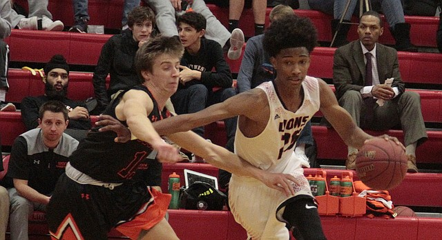 Lawrence High junior Savonni Shazor drives to the rack against Shawnee Mission Northwest senior George Specht in the first half of the Lions' 77-51 victory over the Cougars on Tuesday at LHS.