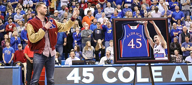 Former Kansas center Cole Aldrich looks up to the rafters where his jersey now hangs during a halftime ceremony.