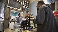 Aunt Netter's Cafe employee Erica Souter hands a receipt to Jeff Ball, of Perry, after taking his order on Thursday, Feb. 15, 2018 at the shop in Lecompton. The business, which is an anchor of downtown Lecompton located at 330 Elmore St., was started with an E-Community loan.