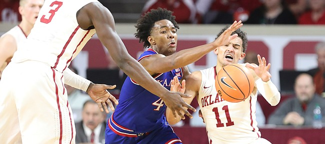 Kansas guard Devonte' Graham (4) is called for a foul on Oklahoma guard Trae Young (11) while trying to knock away a pass from Oklahoma forward Khadeem Lattin (3) during the second half at Lloyd Noble Center on Tuesday, Jan. 23, 2018 in Norman, Oklahoma.