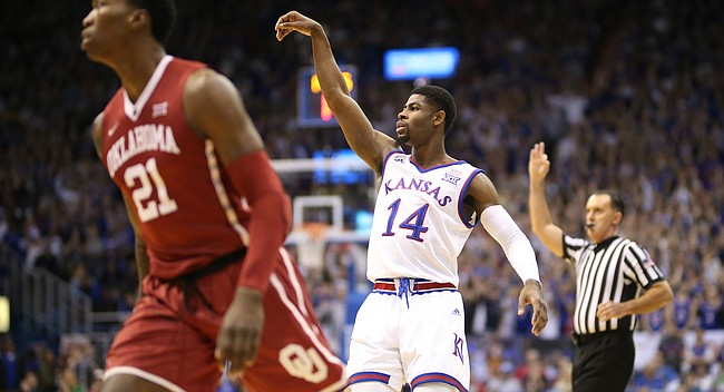 Kansas guard Malik Newman (14) hangs his arm in the air after a three over Oklahoma forward Kristian Doolittle (21) during the first half, Monday, Feb. 19, 2018 at Allen Fieldhouse.