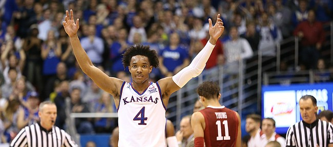 Kansas guard Devonte' Graham (4) raises up the Fieldhouse during a timeout in the second half, Monday, Feb. 19, 2018 at Allen Fieldhouse.
