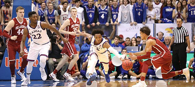Kansas guard Devonte' Graham (4) strips a pass going to Oklahoma guard Trae Young (11) during the second half, Monday, Feb. 19, 2018 at Allen Fieldhouse.