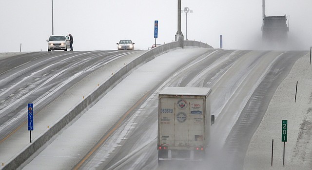 A motorist stops to clear ice from his wipers along I-70 near Lawrence, Kan., Tuesday, Feb. 20, 2018. The area is under a winter weather advisory. (AP Photo/Orlin Wagner)
