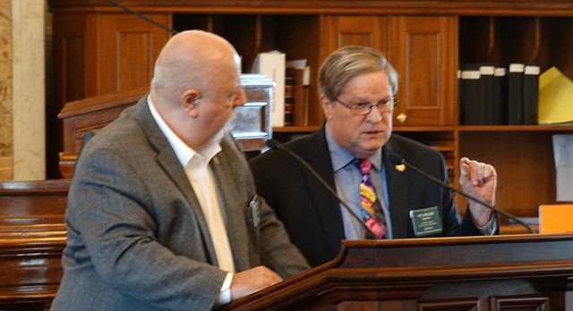 Rep. Vic Miller, right, answers questions from Rep. Michael Houser during debate in the Kansas House about a bill to require candidates for statewide office to be at least 18 years of age.
