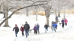 Lawrence resident, Dayag Anashiym, leads a line of 11 homeschooled children on a quick jog around the slushy path at Buford Watson Park, on Tuesday, Feb. 20, 2018 in downtown Lawrence.