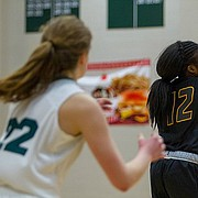 Free State's Caely Kesten (13) gets around a Shawnee Mission West player to pass to her teammate Erin Cushing (22) during the Firebirds' home game on Friday, Feb. 23, 2018. Free State won, 47-38.