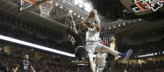 Kansas guard Devonte' Graham (4) puts up a shot and draws a foul from Texas Tech center Norense Odiase (32) during the second half on Saturday, Feb. 24, 2018 at United Supermarkets Arena.