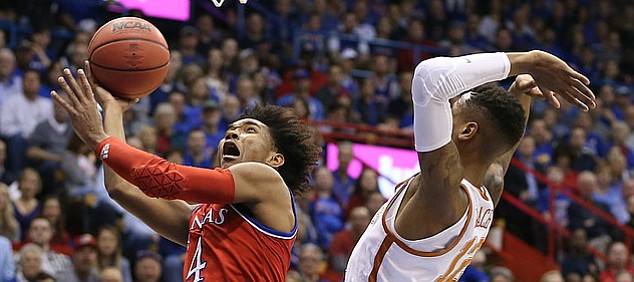 Kansas guard Devonte' Graham (4) elevates to the bucket past Texas guard Kerwin Roach II (12) during the first half on Monday, Feb. 26, 2018 at Allen Fieldhouse.