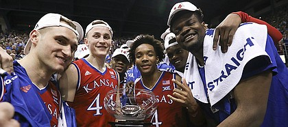 The Jayhawks come together with the Big 12 conference championship trophy following their 80-70 win over Texas on Monday, Feb. 26, 2018 at Allen Fieldhouse. The win gave the Jayhawks an outright win of their 14th-straight Big 12 Conference title.