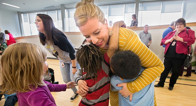 Sunset Hill kindergarten teacher Nicole Corn gets hugs from several of her students after an assembly in which Corn received a surprise recognition on Tuesday, Feb. 27, 2018, as the district's 2018 elementary teacher of the year. Many of Corn's family members attended the assembly, where she was also presented with a $1,000 check.
