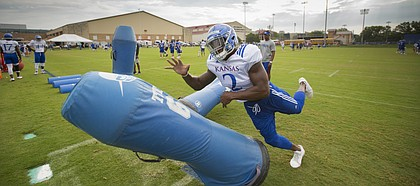 Kansas defensive end Dorance Armstrong hits a dummy while running through a drill during practice on Friday, Aug. 18, 2017 at the grass fields adjacent to Hoglund Ballpark.