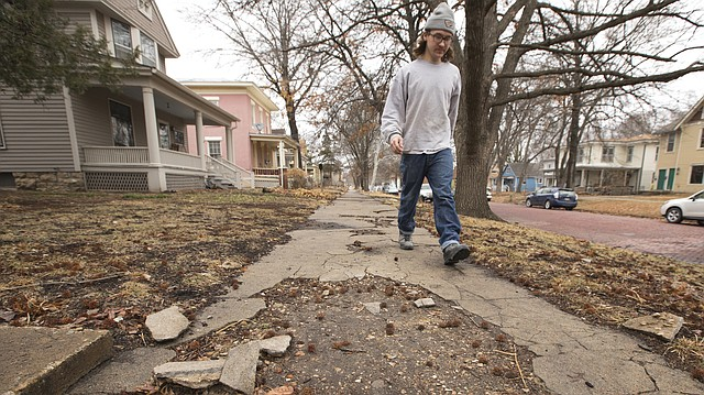 Lawrence resident Ryan Fitzpatrick makes his way south along the 900 block of Rhode Island Street past a section of crumbling sidewalk on Wednesday, Feb. 28, 2018.