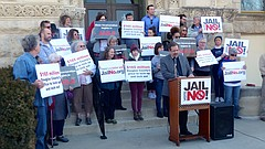 Justice Matters co-chairman Ted Mosher speaks from a lectern in front of the Douglas County Courthouse as he and other activists kick off their campaign against the proposed expansion of the Douglas County Jail on Saturday.