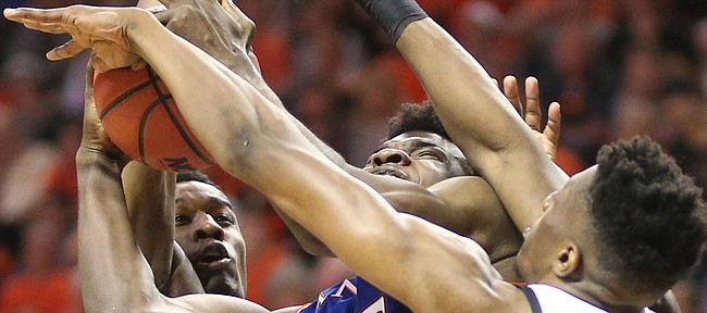 Kansas center Udoka Azubuike (35) gets tied up between Oklahoma State forward Cameron McGriff (12) and Oklahoma State forward Yankuba Sima (35) during the first half, Saturday, March 3, 2018 at Gallagher-Iba Arena, in Stillwater, Okla.