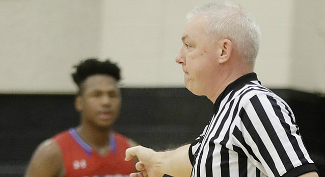 High school basketball official Phil Lombardi signals a foul to the scorer's table in Saturday's game between Free State and Bishop Miege at FSHS.