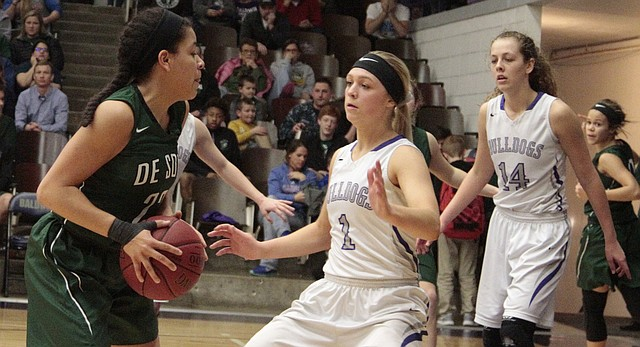 Baldwin senior Reilly Stewart (1) slides in front of De Soto junior Linnea Searls in the Bulldogs' 58-39 win over the Wildcats on Feb. 23 at BHS.