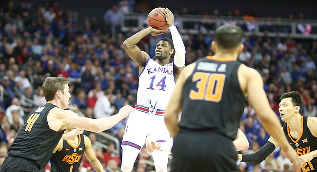 Kansas guard Malik Newman (14) pulls up for a three between several Oklahoma State players during the first half, Thursday, March 8, 2018 at Sprint Center in Kansas City, Mo.