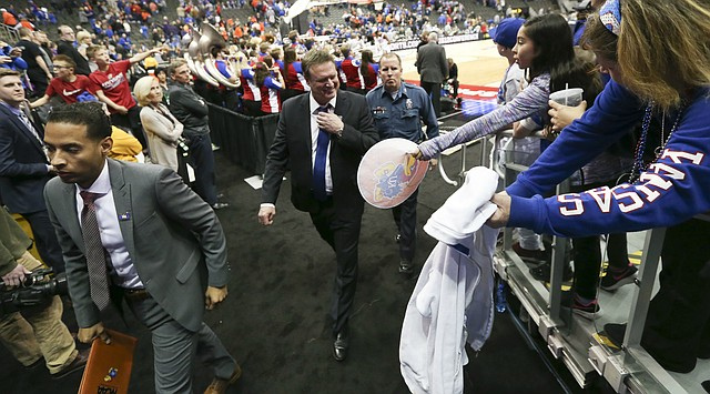Kansas head coach Bill Self loosens his tie as he makes his way from the court following the Jayhawks' 82-68 win over Oklahoma State, Thursday, March 8, 2018 at Sprint Center in Kansas City, Mo.